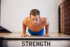 Bare Chested Man In Gym Doing Press-Ups Stock Image