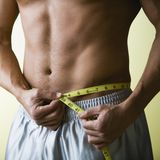 Bare Chested Man Measuring Wai. Muscular Young Man with Bare Chest Measuring Waist Royalty Free Stock Photography