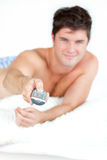 Bare-chested man with pajamas using remote on bed Royalty Free Stock Images