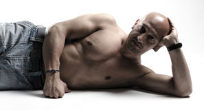 Bare chested man on studio floor Royalty Free Stock Photography