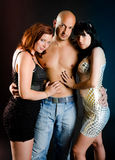 Bare chested man and two women Royalty Free Stock Photography