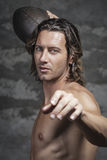 Bare chested model is throwing football ball. Bare chested long hair model is  throwing football ball in camera Stock Image