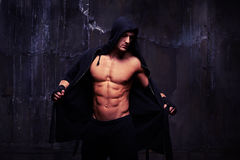 Bare-chested muscular athlete taking off a black hoodie Royalty Free Stock Photos