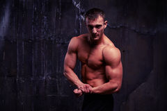 Bare-chested muscular young man pumped his arm Stock Image