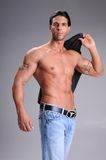 Bare Chested Young Man. Muscular young man standing bare chested in jeans with a black long sleeve dress shirt over his shoulder Royalty Free Stock Photos
