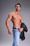 Bare Chested Young Man. Muscular young man standing bare chested in jeans with a black long sleeve dress shirt over his arm Stock Photography