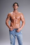Bare Chested Young Man. Muscular young man standing bare chested and sweaty in jeans Royalty Free Stock Photos