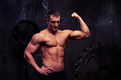 Bare-chested young strong sportsman standing half-turned and fle Stock Photo