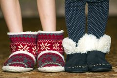 Bare child legs and feet in red winter christmas boots with ornament pattern.  royalty free stock image