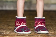 Bare child legs and feet in red winter christmas boots with orna. Ment pattern Stock Photography