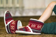 Bare child legs and feet in red winter christmas boots with orna. Ment pattern Stock Images