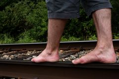 Bare feet. Two white bare feet of a Caucasian male balancing on rails stock image