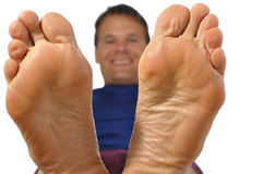 Bare feet. Closeup of bottom of feet as smiling man reclines on white background Stock Image