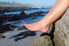 Bare feet. Beautiful female caucasian bare feet of a young teenage woman model with pink nailpolish, full of sand, in front of a rocky beach and the sea in royalty free stock image