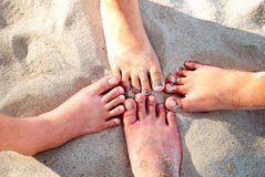 Bare Feet. Two pair of bare feet covered by beach sands stock image