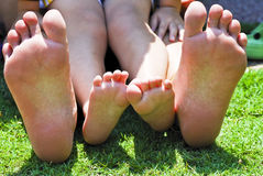 Bare Feet. Kid and women bare feet sit on field Stock Photos