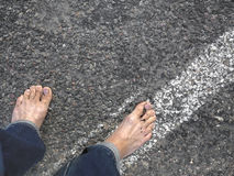 Bare Feet On Asphalt. Man walking on asphalt road with bare feet, above cropped view Stock Image