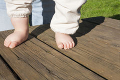 Bare feet of a baby doing his first steps. Over weathered wooden background. Natural light Stock Photography