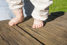 Bare feet of a baby doing his first steps. Over weathered wooden background. Natural light Royalty Free Stock Photo