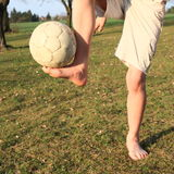 Bare feet with ball. Bare feet of a young teenager - boy standing on grass of meadow and playing with football ball Royalty Free Stock Photo