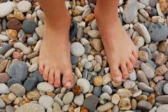 Bare feet on beach. Bare wet feet standing on rock gravel beach Royalty Free Stock Image