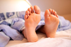 Bare feet in bed Royalty Free Stock Image