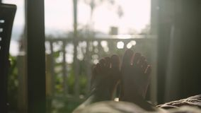 Bare feet dancing in the bed in early morning in the sun with beautiful lens flare effects. slow motion. 3840x2160. Bare feet in the bed in early morning in the stock footage
