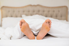 Bare feet in bed at home Royalty Free Stock Photography