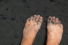 Bare feet on black sand beach. Bare feet partially covered with black sand on black sand beach Royalty Free Stock Images