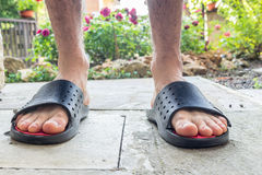 Bare feet of boy in black slippers. With hairy legs in your back yard Stock Photography