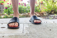 Bare feet of boy in black slippers. With hairy legs in your back yard Stock Photo