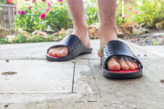 Bare feet of boy in black slippers. With hairy legs in your back yard Stock Images