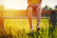 Bare feet of a boy hang down from a bench. In a summer park at sunset stock images