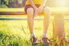 Bare feet of boy hang down from bench in summer park. At sunset stock image