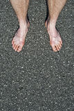 Bare feet on cement. Close-up of male bare feet on cement vertical shot Royalty Free Stock Photos