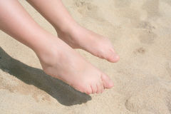Bare feet of child on sand, Stock Images