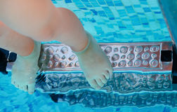 Bare feet of a child standing on pool steps Stock Images