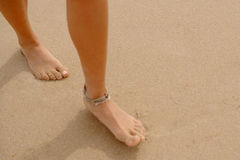 Bare Feet Coated in Sand Walking on Beach. Close Up of Woman Wearing Ankle Bracelet Walking on Beach with Bare Feet Coated in Sand  Footprints and Copy Space to Stock Photography