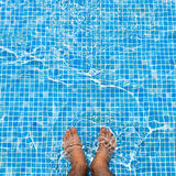 Bare feet cooling off in the pool relaxing concept squ Stock Photo