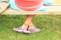Bare feet in crocks. Little girl with bare feet in purple crocks on grass sitting on bench Royalty Free Stock Photo