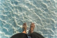 Man`s foot in warm clear water in the Dead sea stock image