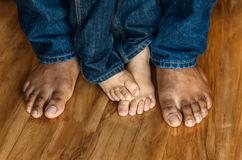 Bare feet of father and son. On a wooden floor background Stock Photo