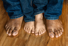 Bare feet of father and son. On a wooden floor background Royalty Free Stock Image