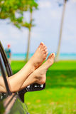 Bare feet of female sticking out car window, by ocean Royalty Free Stock Photography