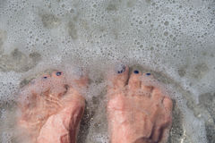 Bare feet in frothy ocean water Stock Photography
