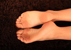 Bare feet on fur Stock Images