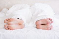 Bare feet of gay couple out from the blanket Royalty Free Stock Image