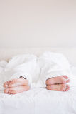 Bare feet of gay couple out from the blanket Royalty Free Stock Images