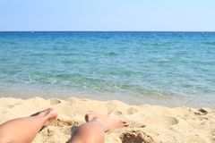 Bare feet on beach. Bare feet of a girl lying in sand on beach by water of sea Royalty Free Stock Images