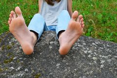 Bare feet of girl on stone. Bare feet of young girl laying on big grey stone on green grass background with copy space for text on rock. Young woman wearing stock photography